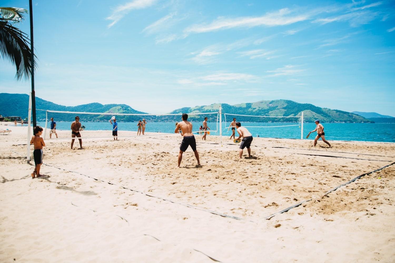 Gruppe von Männern spielt Volleyball am Strand