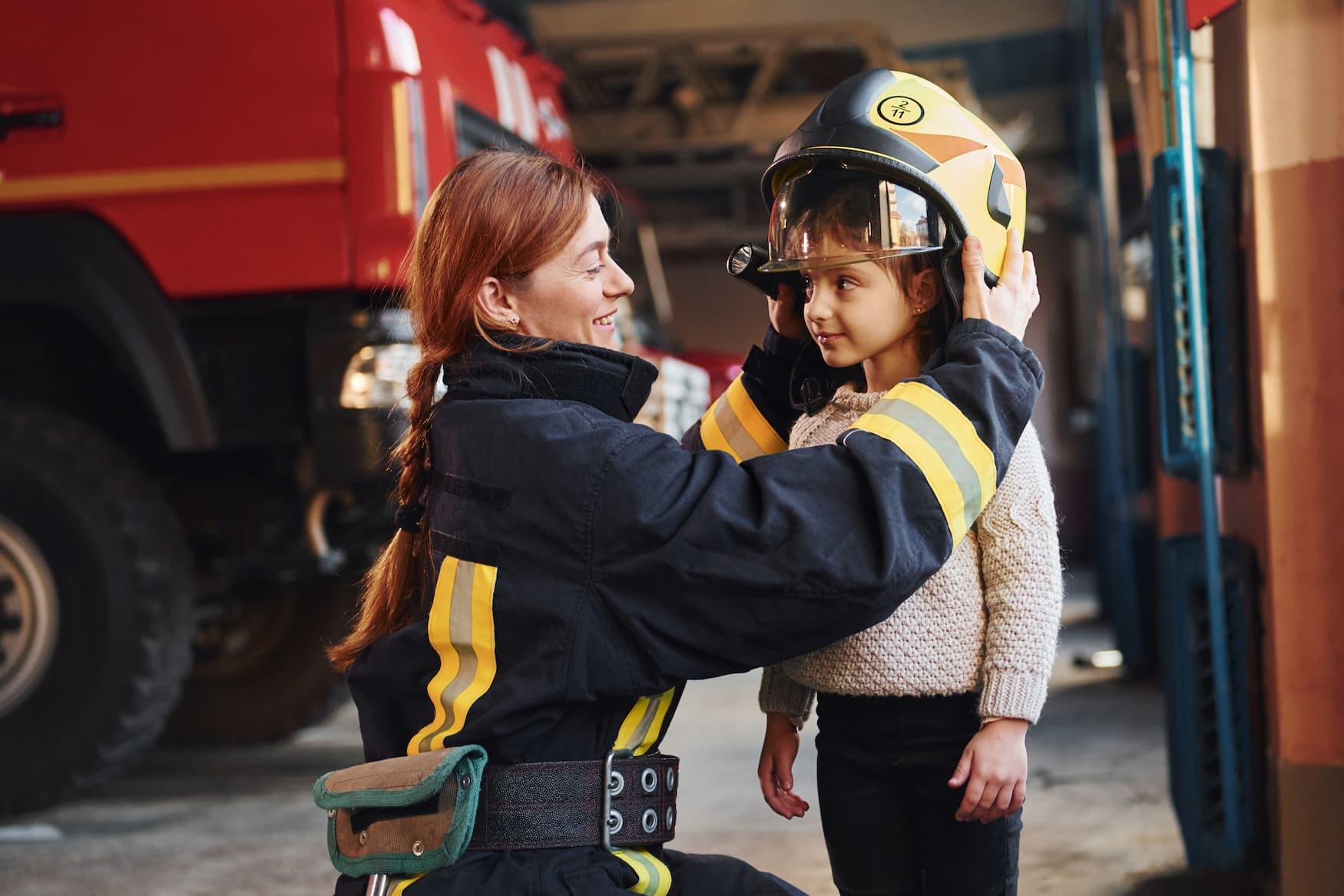 Kleines glückliches Mädchen kriegt Helm von Feuerwehrfrau aufgesetzt