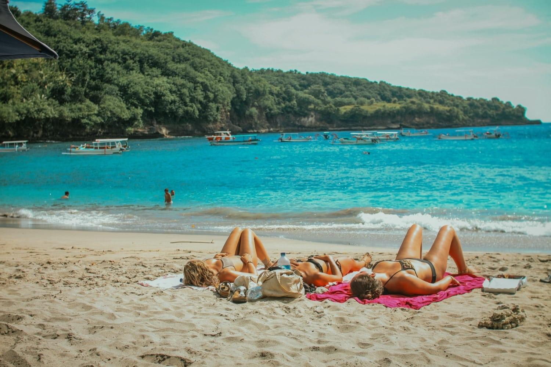 Mädels liegen an Strand und sonnen sich