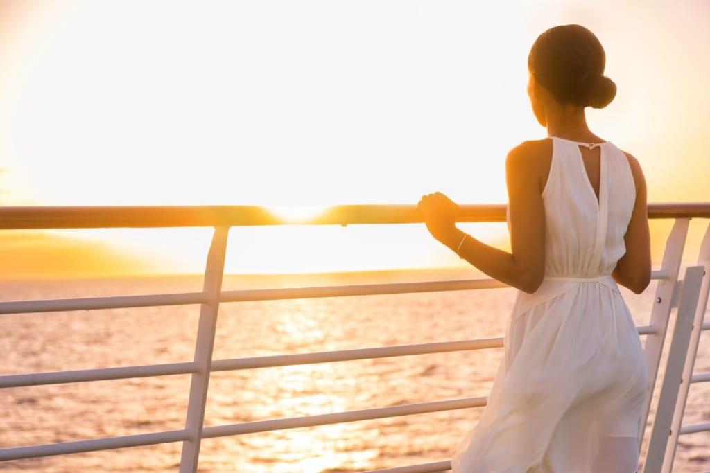Kreuzfahrt Passagierin steht an Reling und blickt aufs Meer