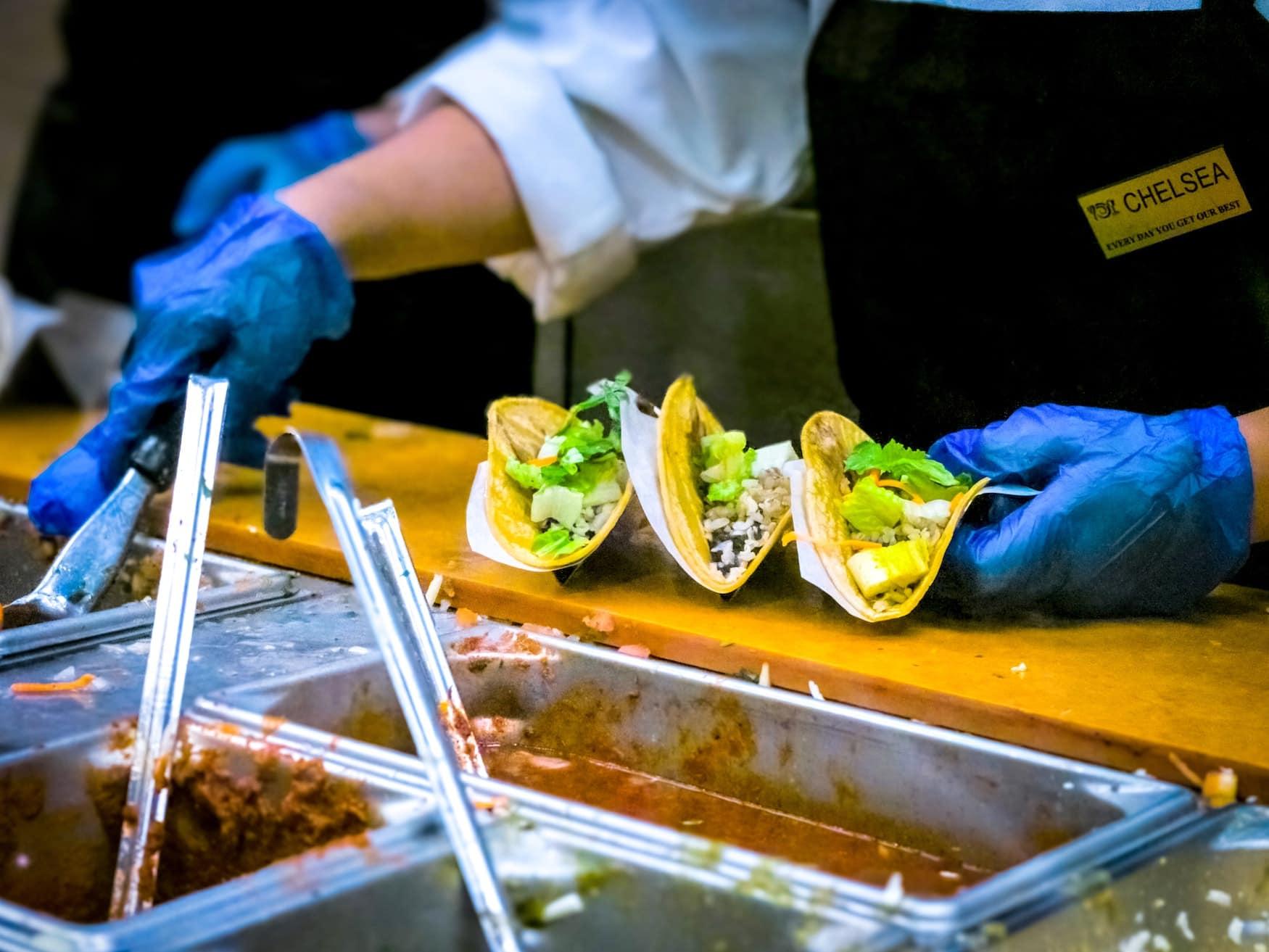 Mann verteilt Guacamole in Tacos auf einem Streed-Food-Markt in Mexiko