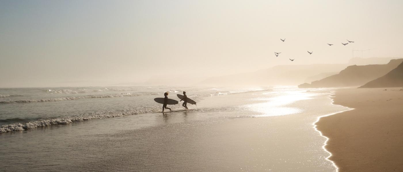Surfer im Surfurlaub an einem Strand in Portugal während Sonnenuntergang