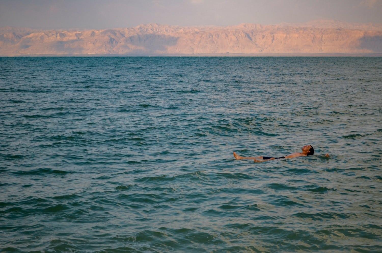 Mann schwimmt an Wasseroberfläche im Toten Meer