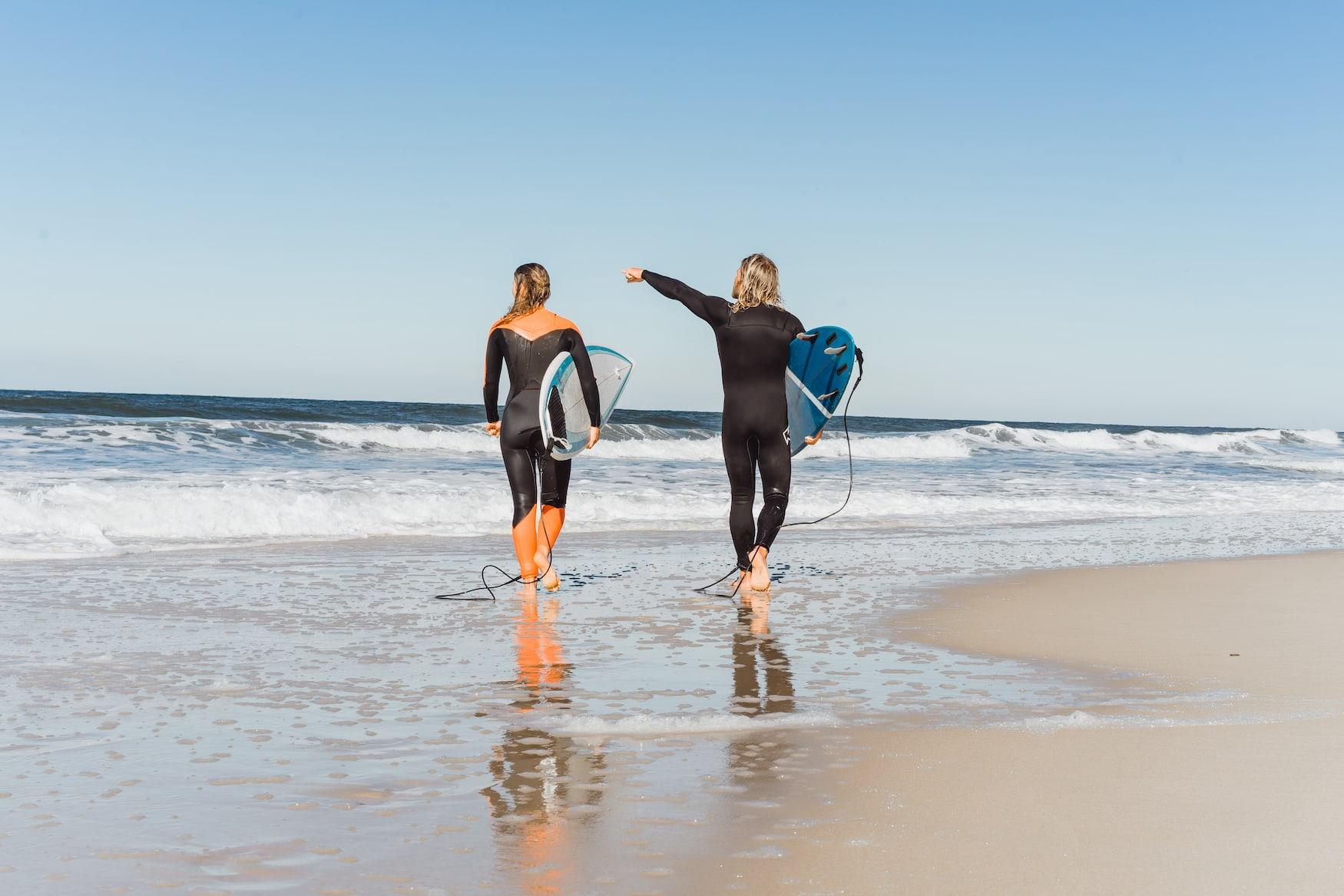 Mann und Frau in Neoprenanzügen spazieren mit Surfbrettern am Strand land