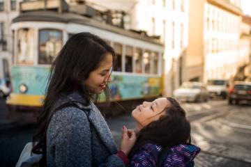 Mutter und Tochter lächeln sich an in Straße in Lissabon, Portugal