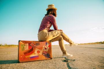 Weltreise: Frau mit langer Hose, Bluse und Hut sitzt auf einem Koffer an einer einsamen Landstraße
