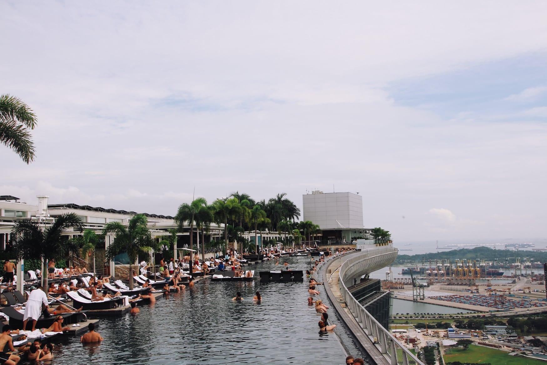 Menschen schwimmen im Infinity Pool auf dem Dach des Marina Bay Sands, eine der Sehenswürdigkeiten in Singapur