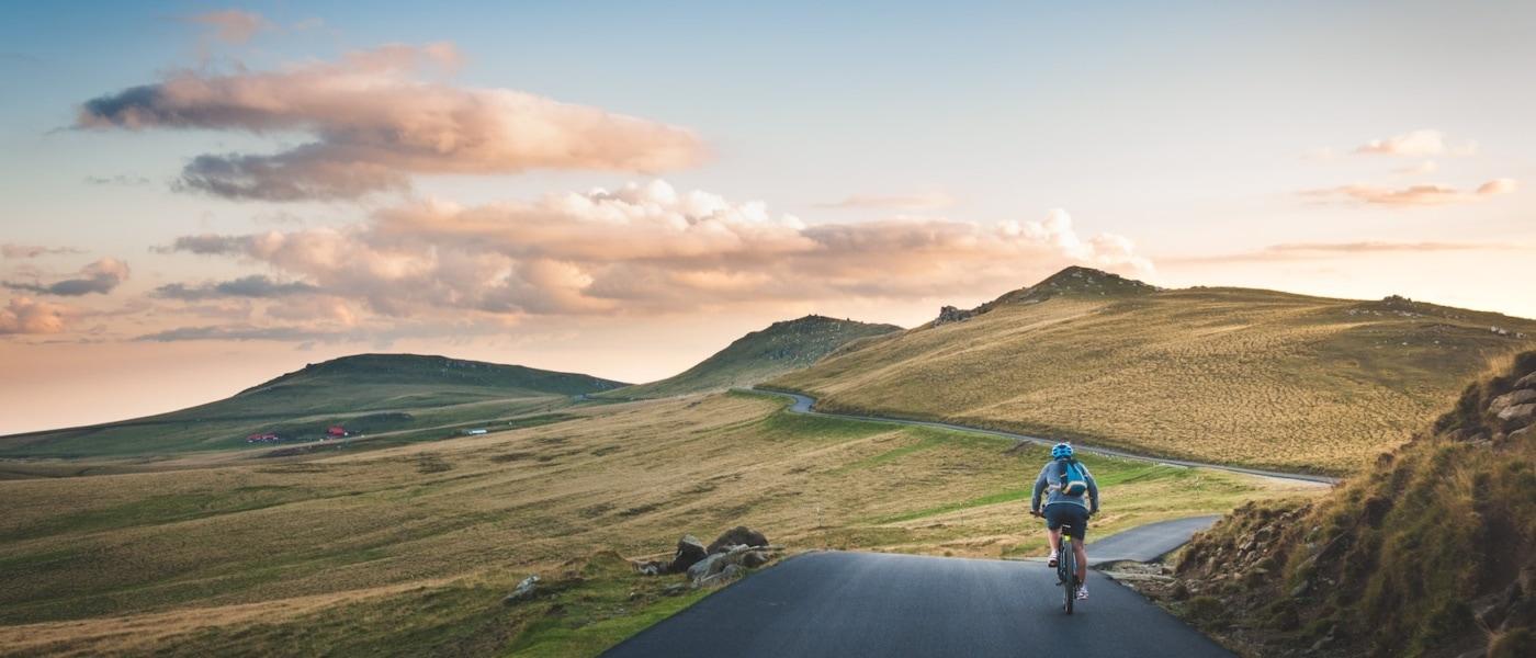 Radwege weltweit: Fahrradfahrer fährt durch bergige Landschaft in Rumänien