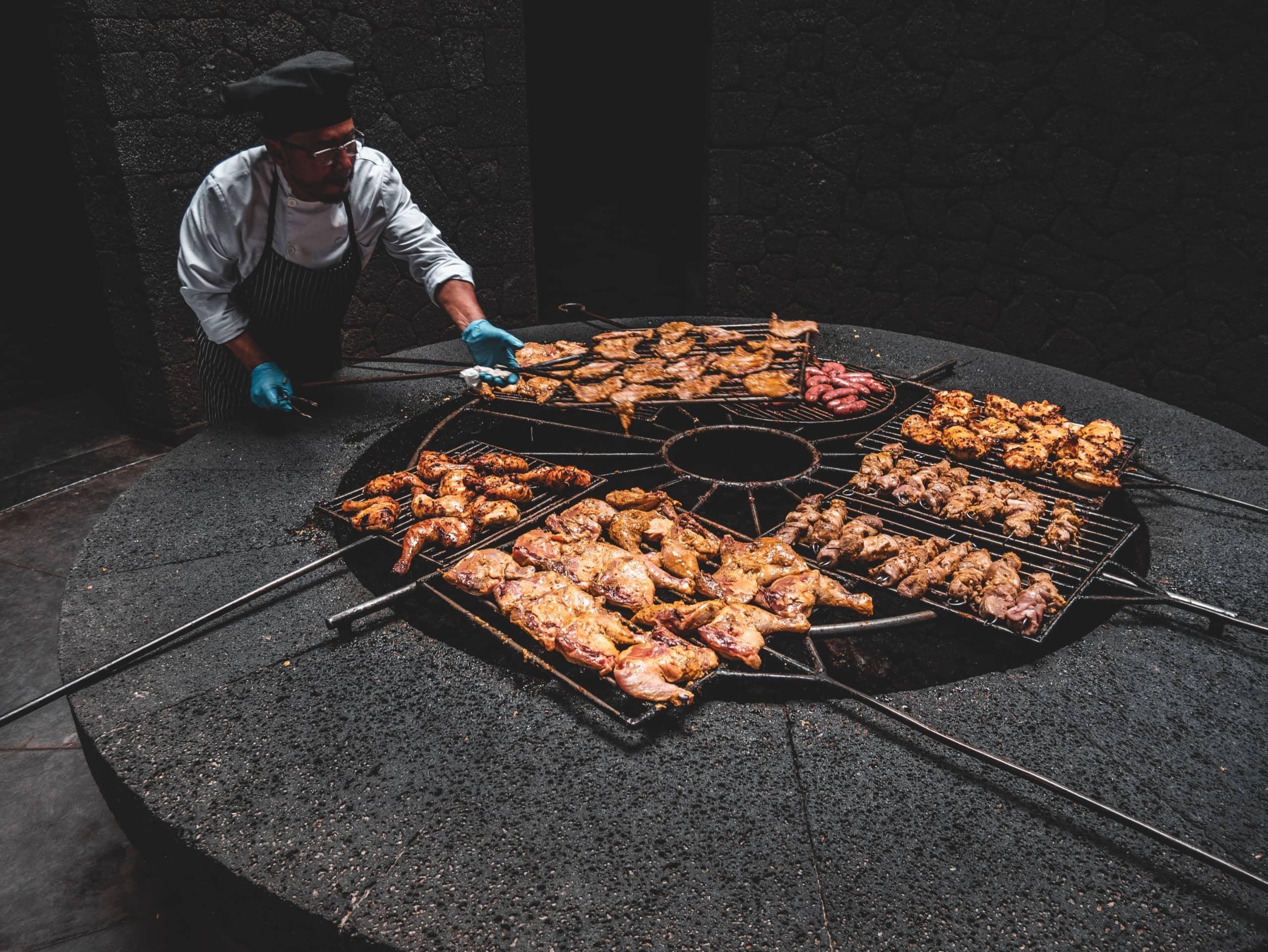 Mann brät Meeresfrüchte und Fleisch im Restaurant Timanfaya auf Lanzarote