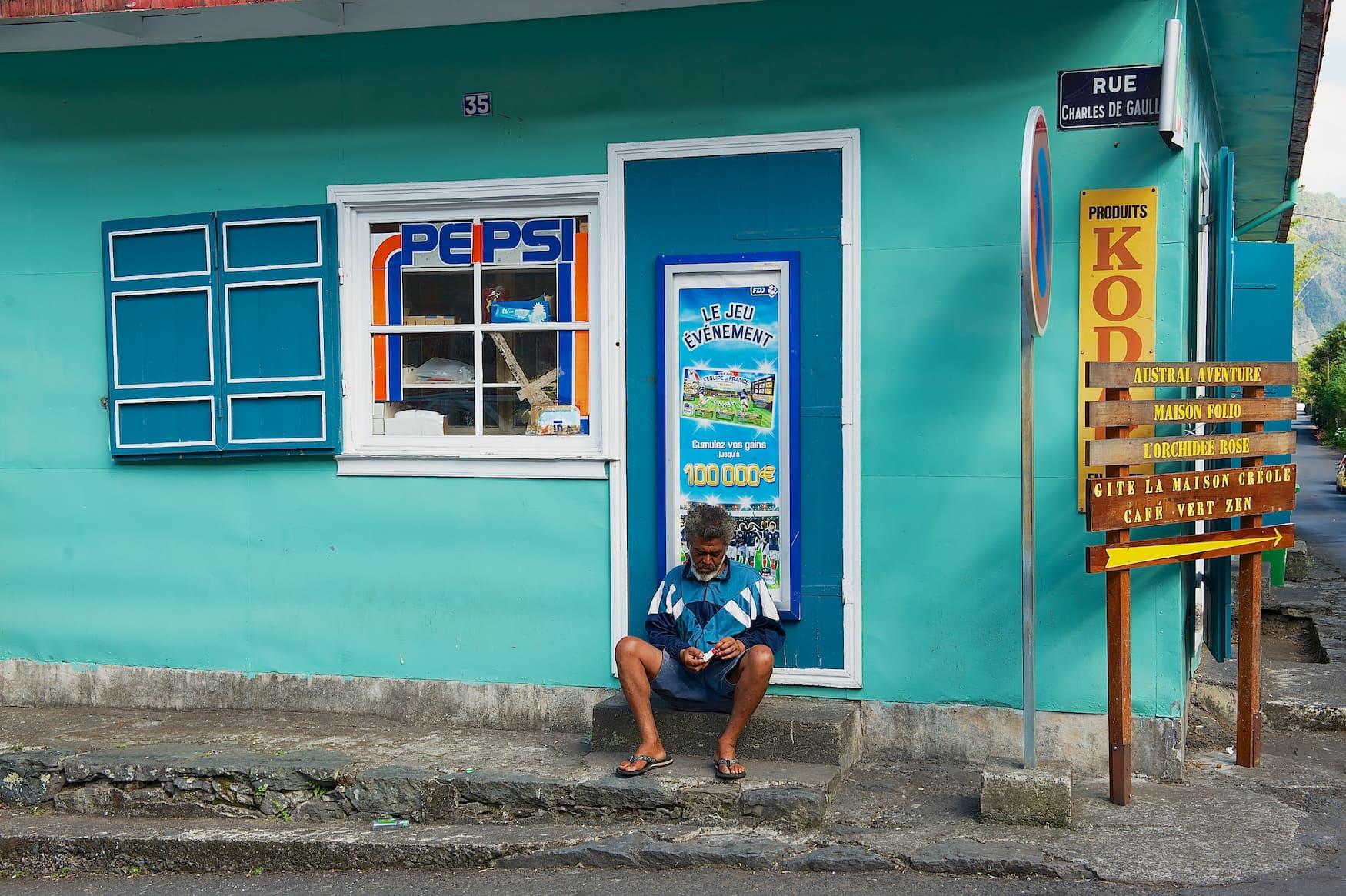 Mann sitzt vor buntem Haus in La Reunion