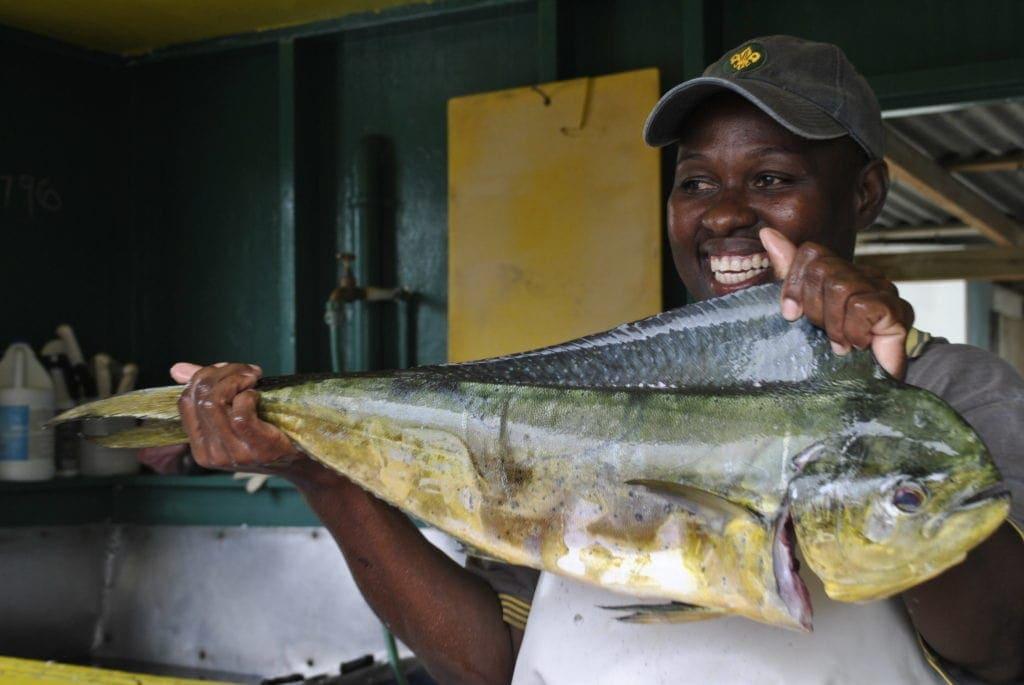 Stolz zeigt eine Fischverkäuferin auf Barbados den Fang des Tages.