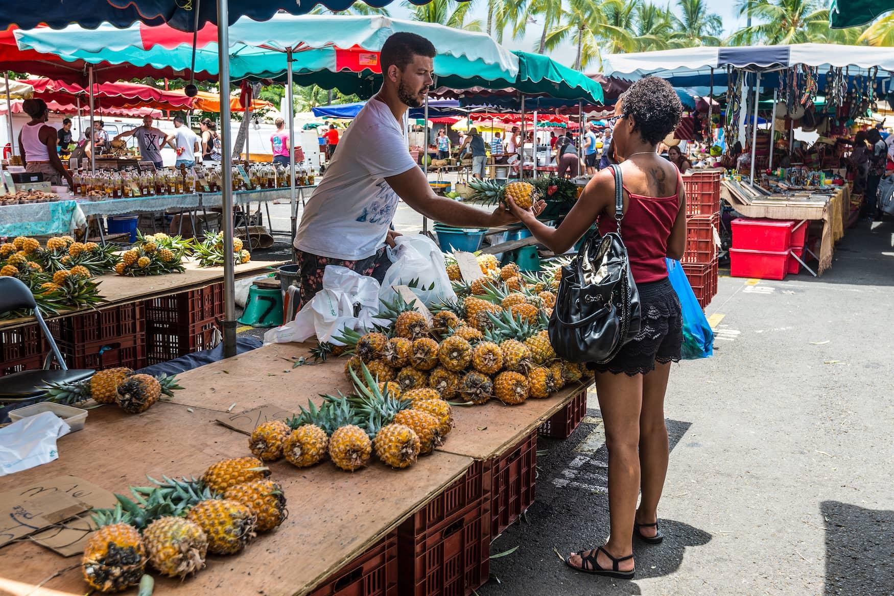 Frau kauft Ananas auf Markt in La Reunion, Frankreich