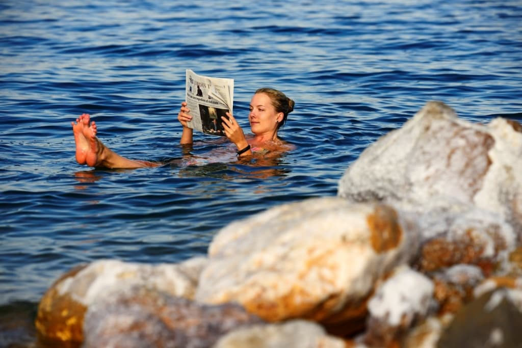 Frau liegt im Toten Meer und liest Zeitung