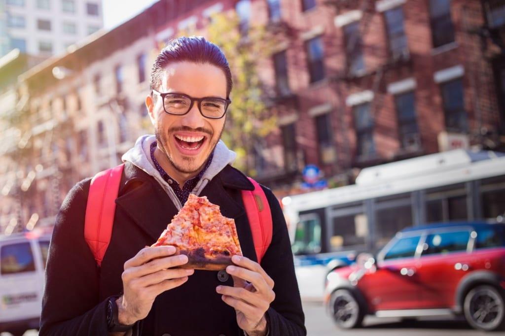 Mann isst Pizza auf Straße