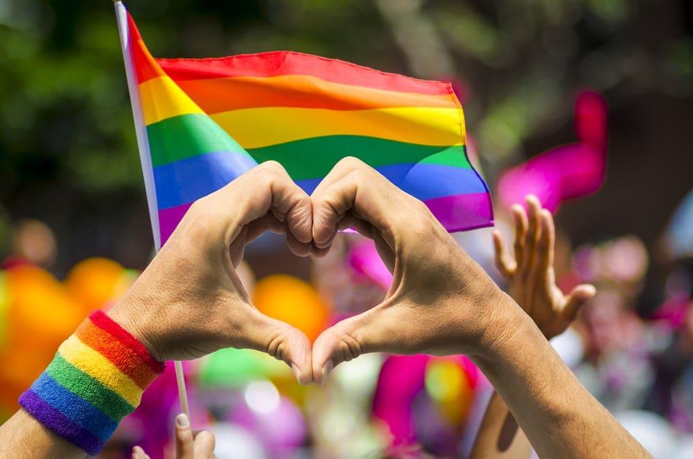 Regenbogenflaggen mit Herz- und Victory-Zeichen