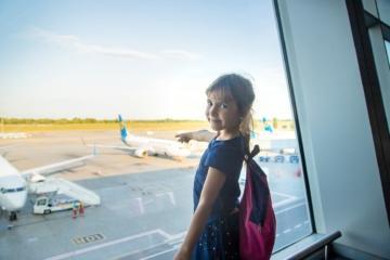 Junges Mädchen fliegt das erste Mal alleine und deutet mit Finger auf das Flugzeug
