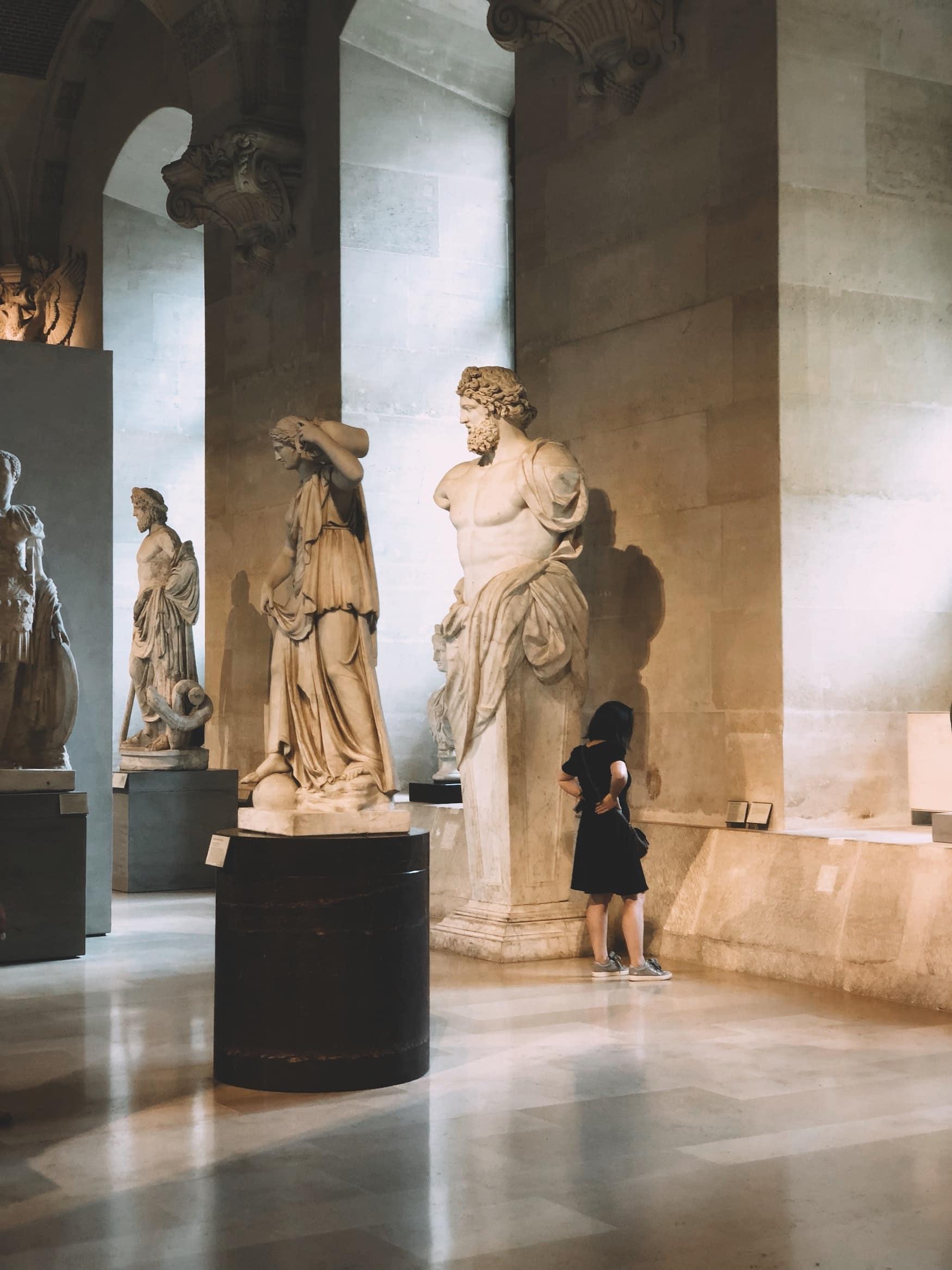 Besucherin guckt sich Statuen im Louvre in Paris an