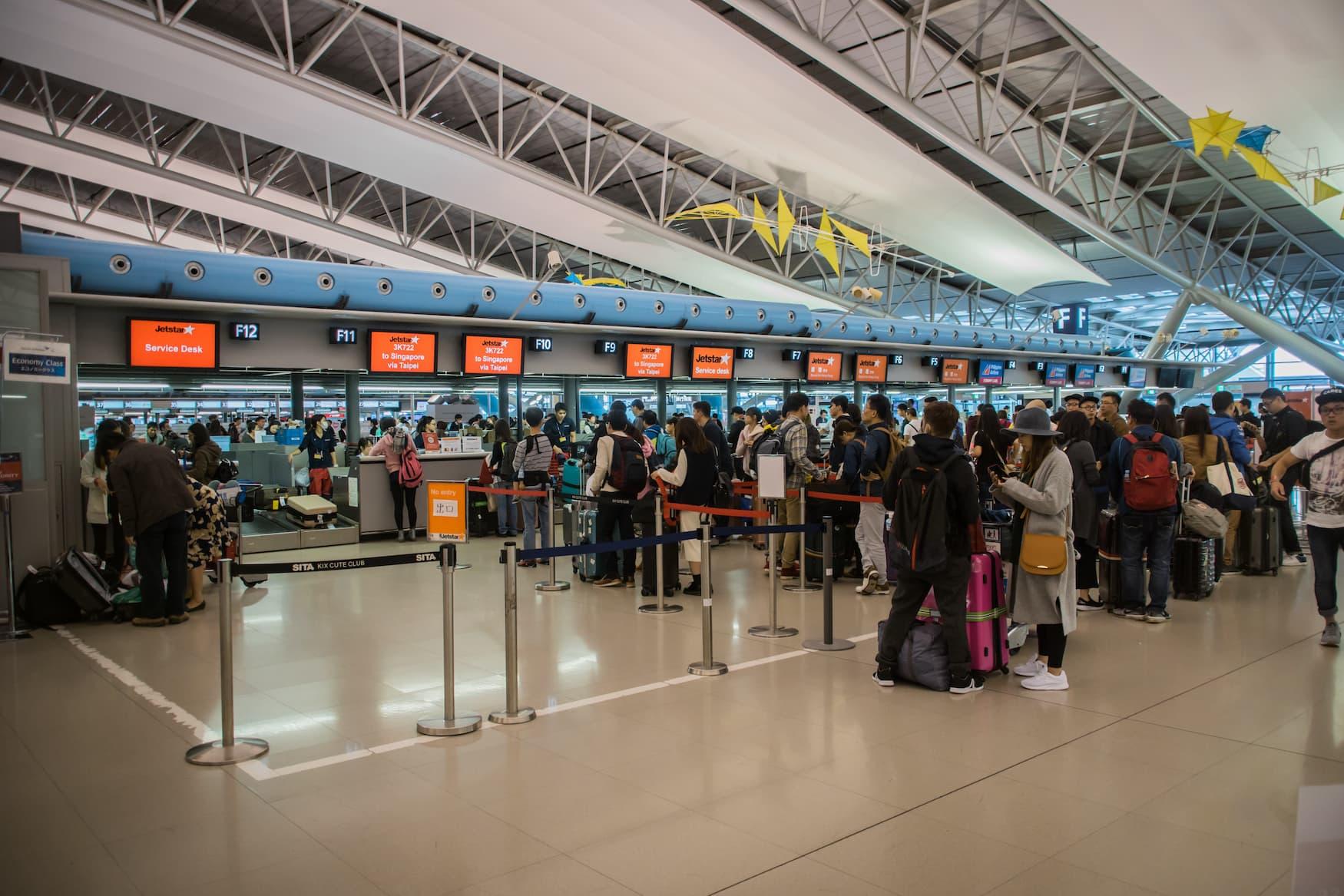 Warteschlange am Check in Schalter am Flughafen in Osaka, Japan