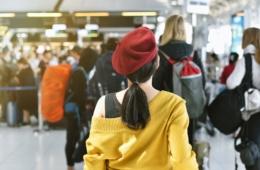 Mädchen mit roter Mütze steht in der Schlange vor dem Check-In-Schalter