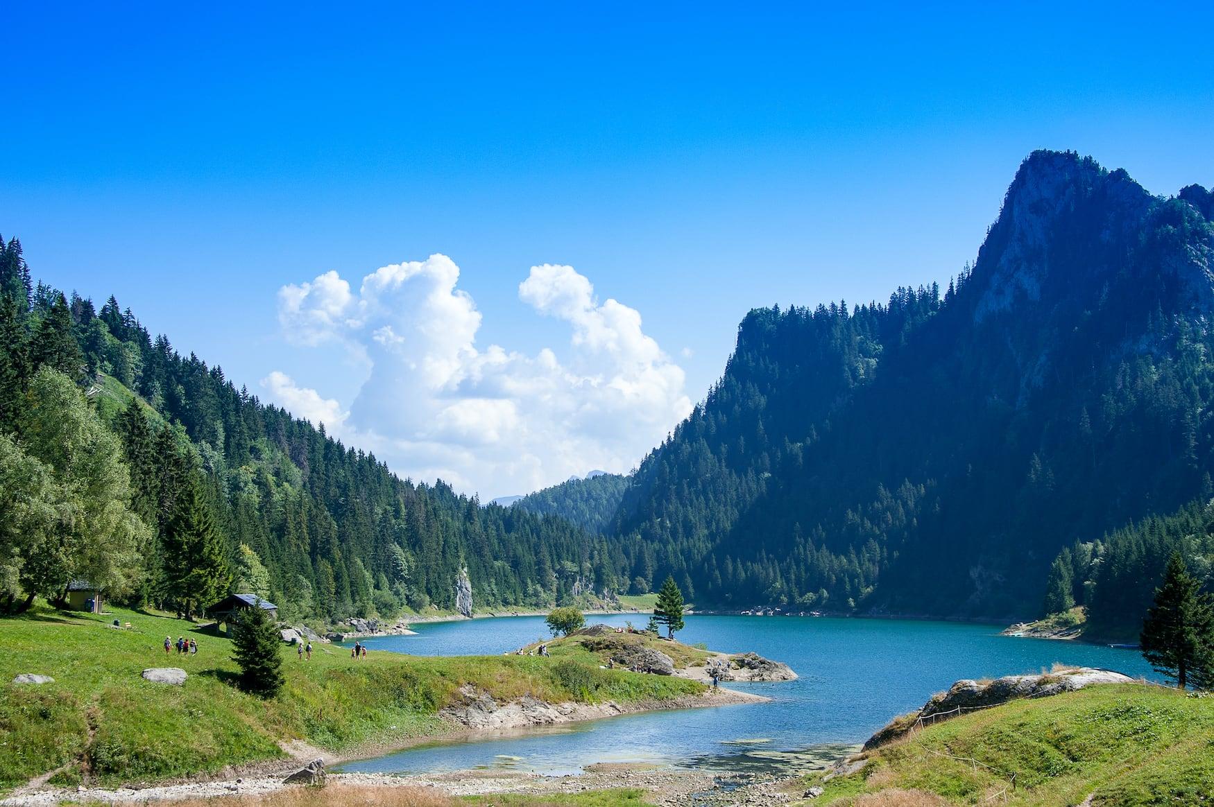 Ruhige Bergseenlandschaft, Lac de Tanay, Schweiz. Klares blaues Wasser eingebettet zwischen grün bewaldeten Gipfeln im Sommer