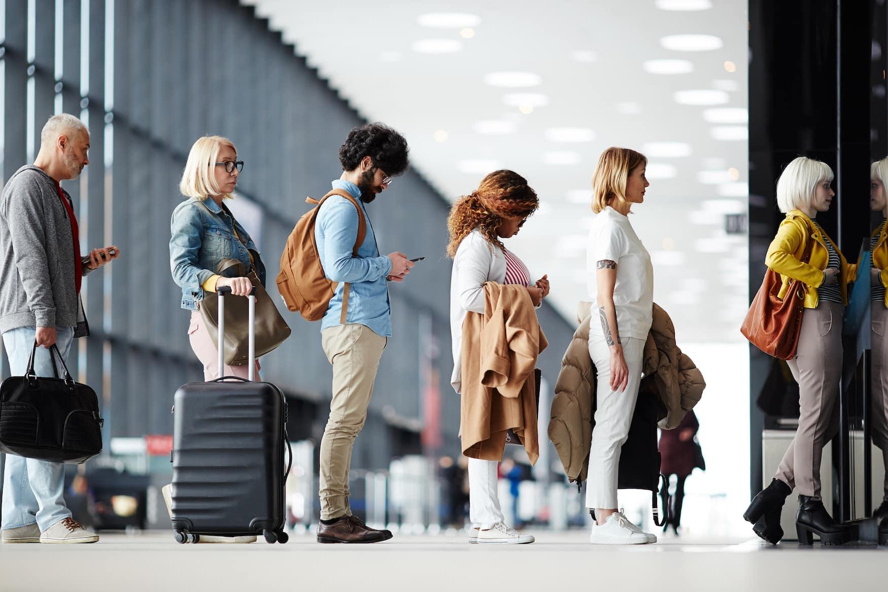 Reisende stehen in Warteschlange am Check in Schalter am Flughafen