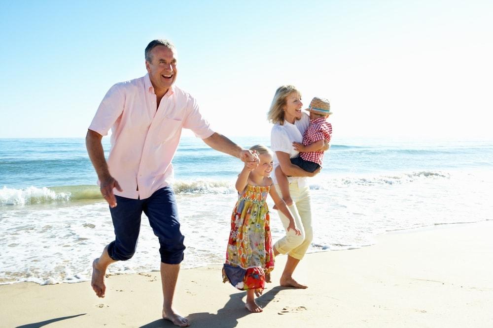 Großeltern mit Kindern am Strand