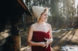 Frau mit Hut und rotem Handtuch kommt aus Sauna