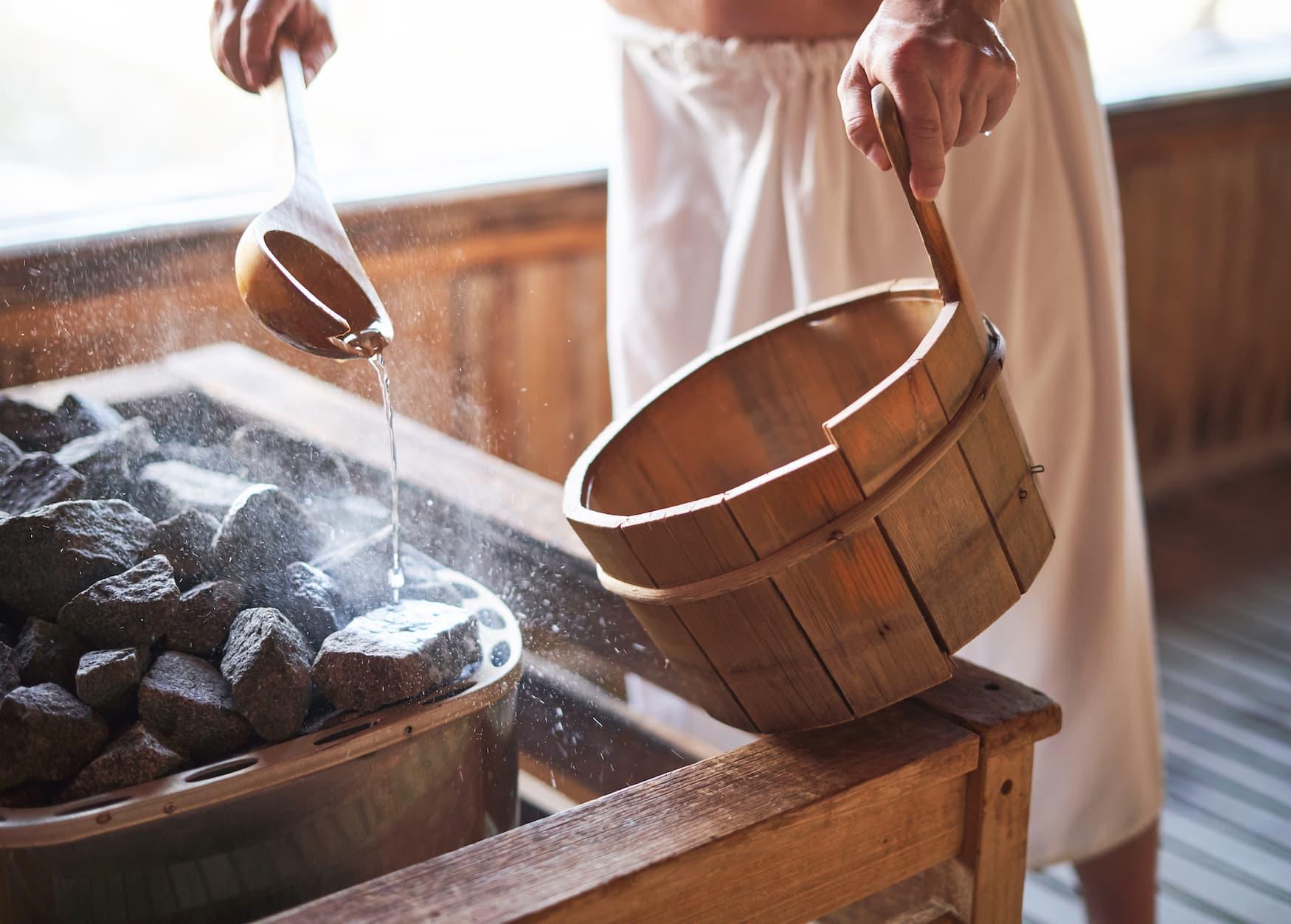 Person leitet einen Sauna-Aufguss und schüttet Flüssigkeit über die heißen Steine