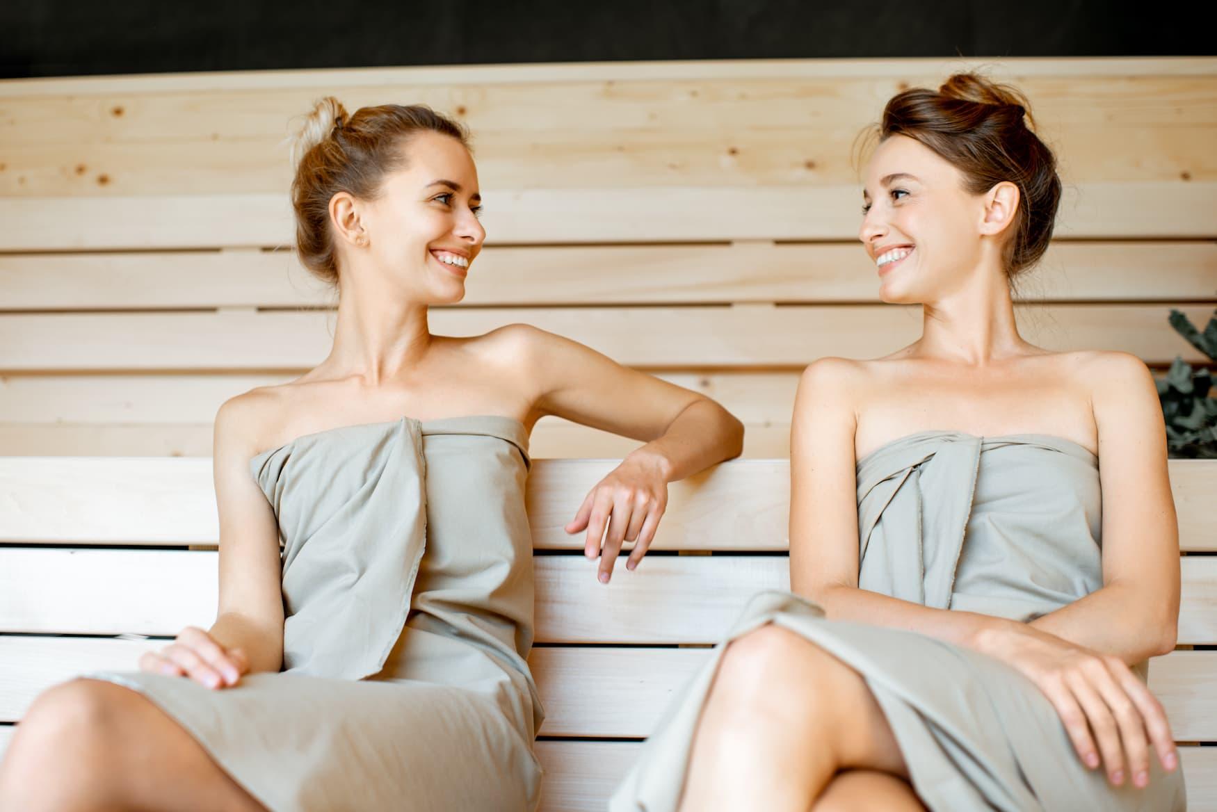 Zwei Freundinnen sitzen in Sauna und reden miteinander