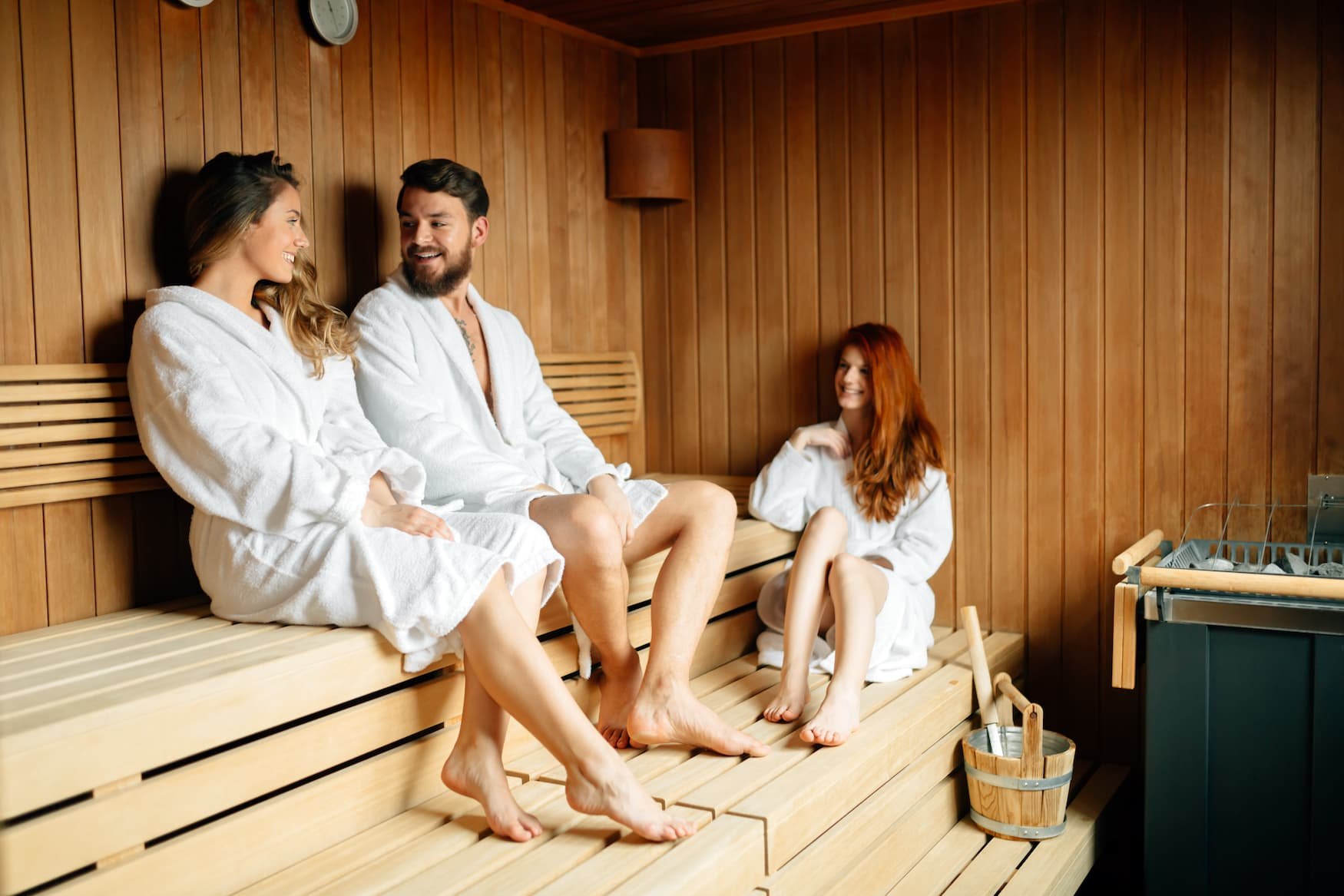 Junger Mann flirtet mit Frauen in der Sauna