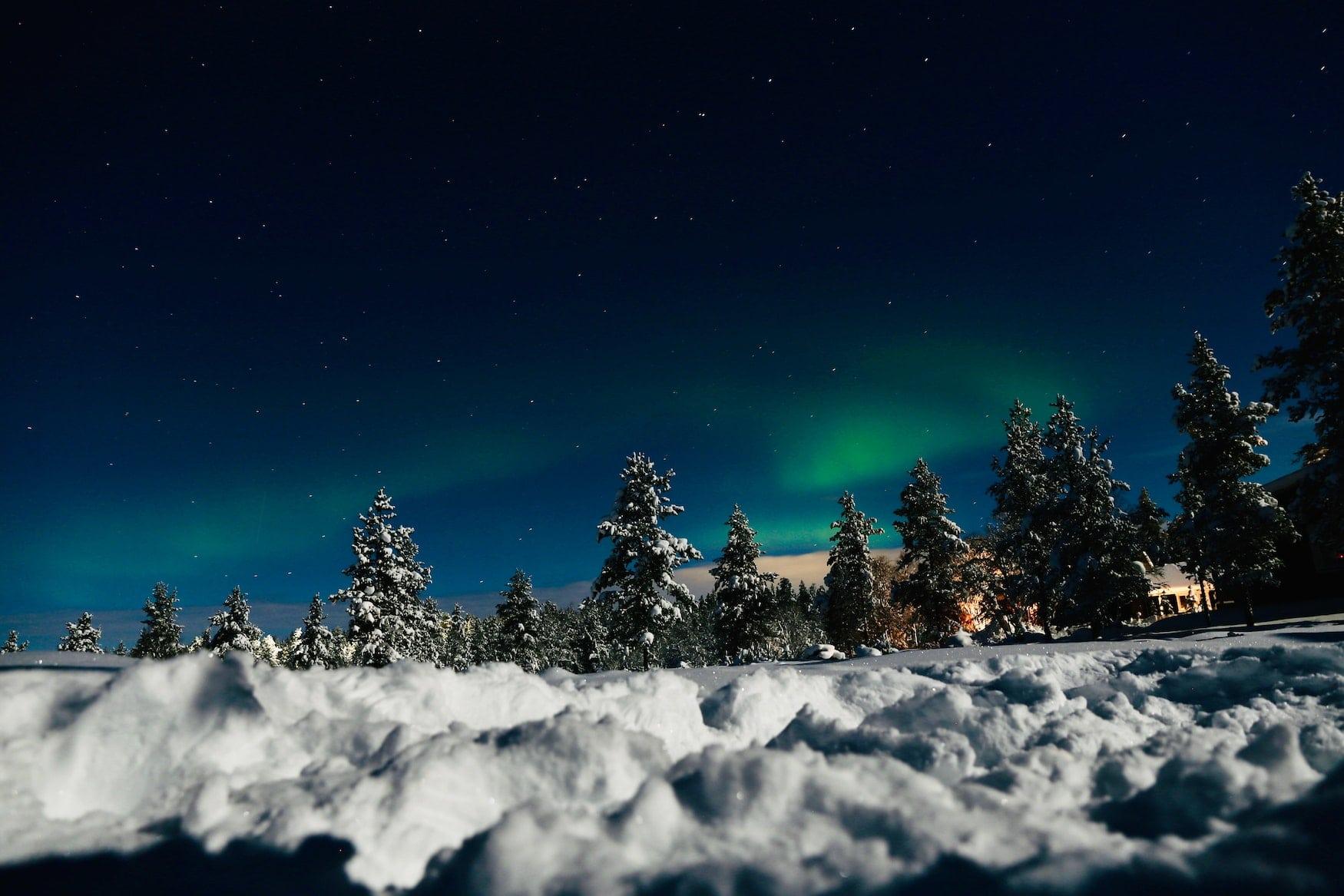 Schnee-Landschaft in Sodankylä, im Hintergrund sind grüne Nordlichter zu sehen