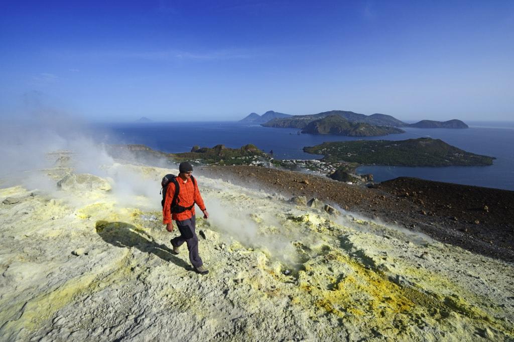 Wanderer auf dem Gran Cratere läuft durch Schwefelfumarolen, Blick auf Lipari, Salinas, Stromboli. Insel Vulcano, Liparische oder Äolische Inseln, Sizilien, Italien, Europa