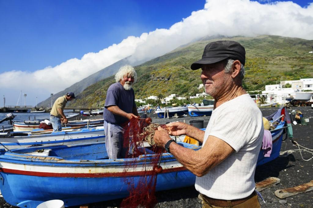 Fischer reparieren Netze am Scari-Strand, im Hintergrund der Vulkan, Insel Stromboli, Liparische oder Äolische Inseln, Sizilien, Italien, Europa