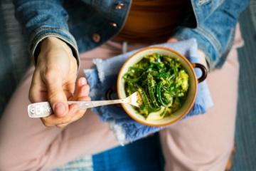 Frau isst Salat aus dem Superfood Algen
