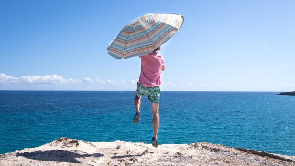 Mann mit Schirm auf Felsen auf Bari