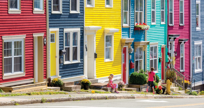 Kinder spielen in sehr bunter Straße vor bunten Häusern