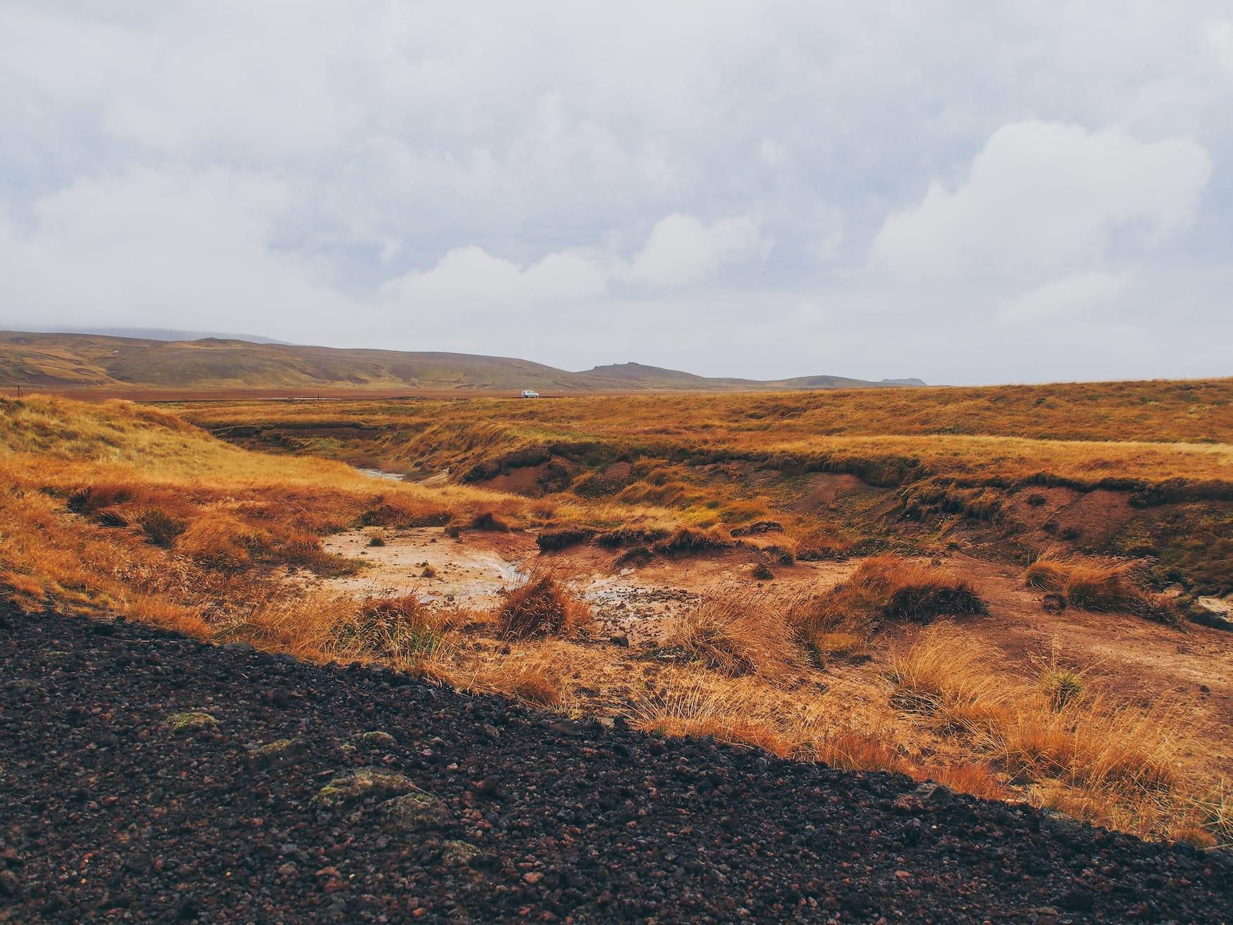 Auto auf verlassener Straße in isländischer Natur