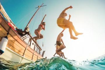 Gäste eines Segelschiffs springen ins Meer