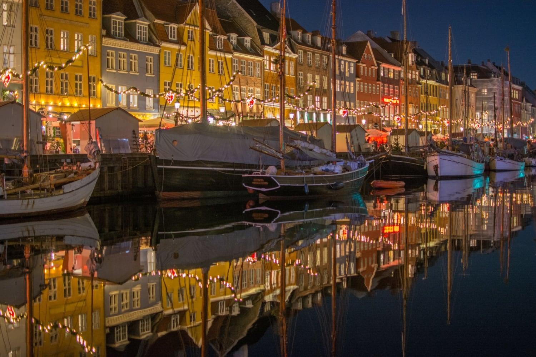 Hafen bei Nacht mit bunten Häusern die sich im Kanal reflektieren
