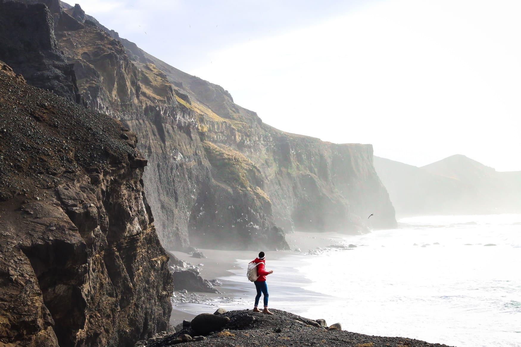 Mann vor Klippen in Island