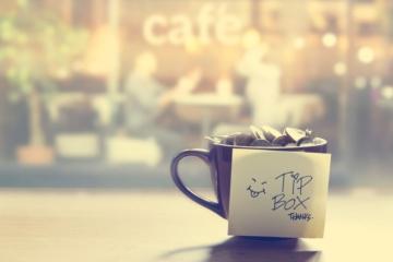 """Tasse mit Trinkgeld-Münzen und einem Zettel mit der Aufschrift """"Tip Box"""""""