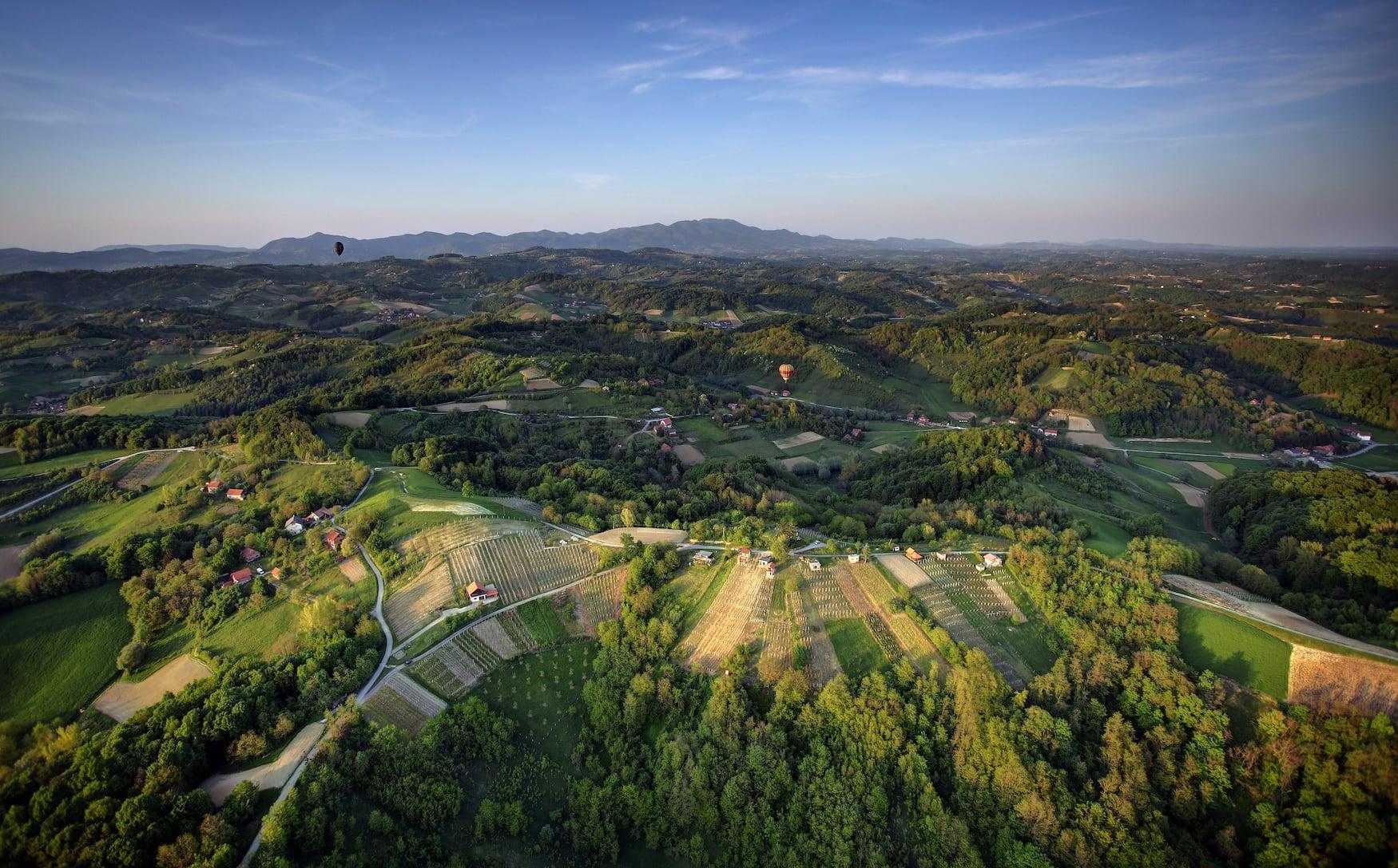 Heißluftballon über grüner Landschaft in Kroatien