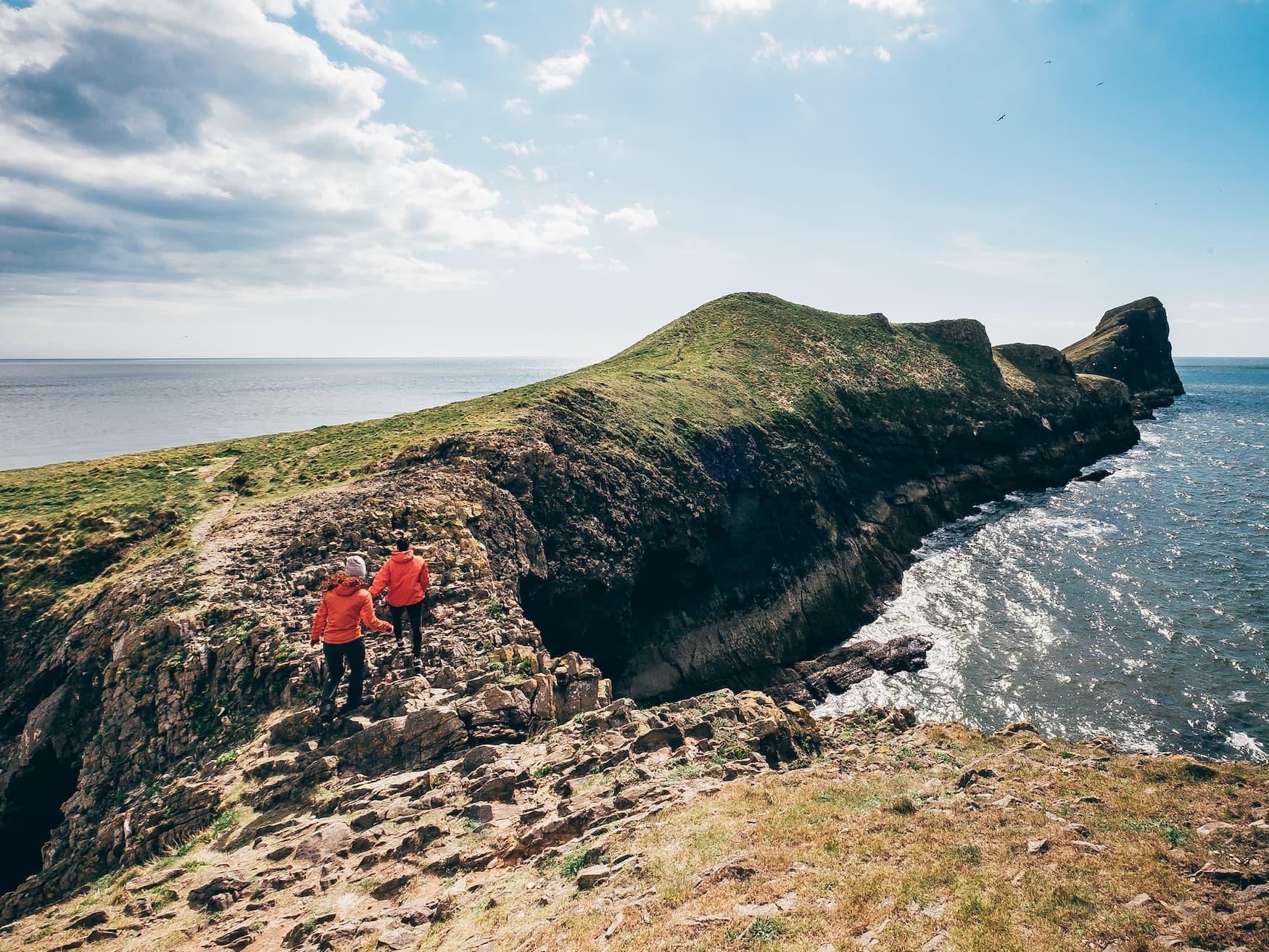 Zwei Frauen wandern entlang der Klippen auf dem Wales Coast Past in der Rhossili Bucht
