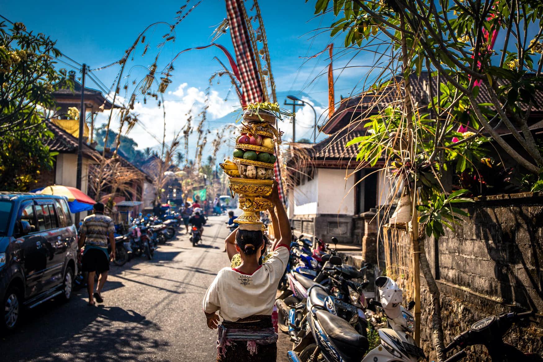 Frau trägt Lebensmittel auf dem Kopf in Dorf auf Bali