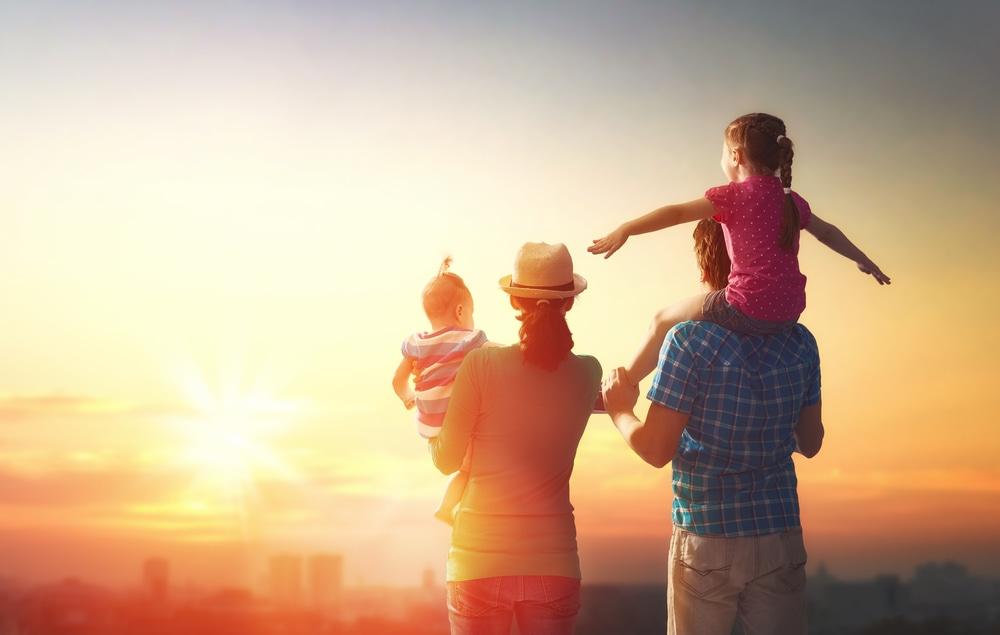 Familie auf Sonnenuntergang blickend