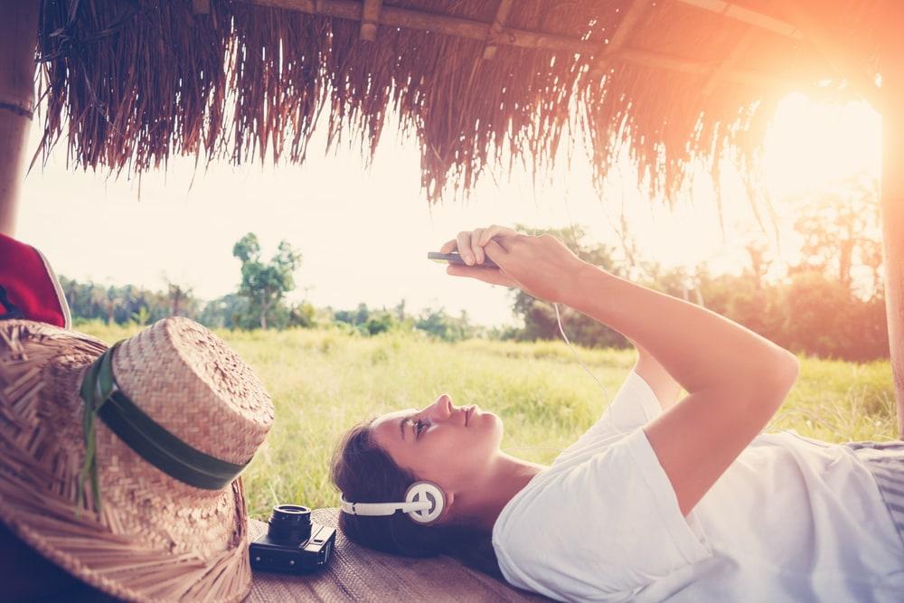 Frau liegt auf Wiese und spielt mit Handy