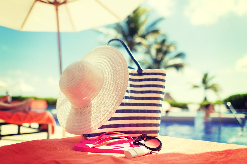 Hut und Handtuch auf Liege am Pool