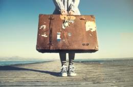 Frau mit Koffer auf einem Steg