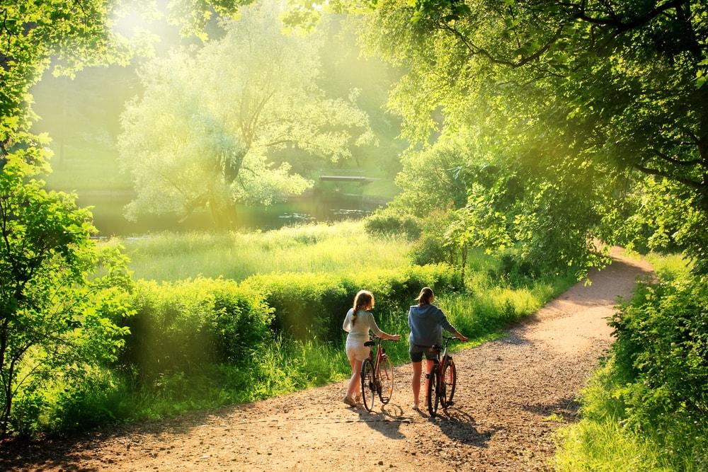 Mädchen mit Fahrrad unterwegs im Wald