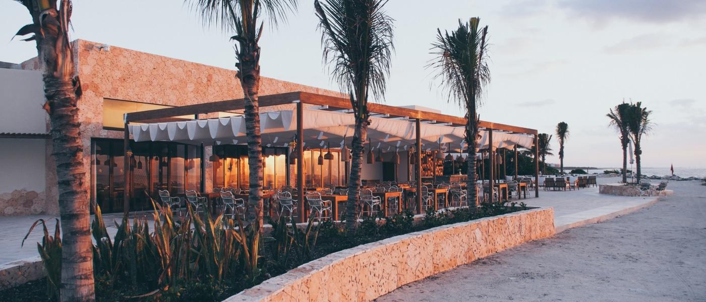 Der Sonnenuntergang taucht die Strandbar Helios in ein rot-orangenes Licht